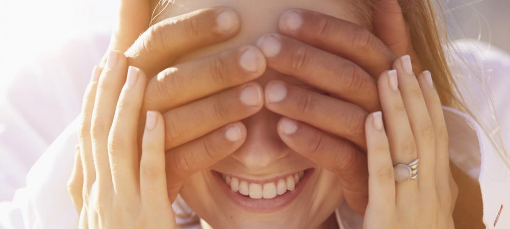 Glückliches Paar: Mann hält lächelnder Frau die Augen zu