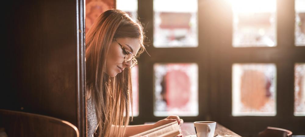 Junge Frau liest ein Buch in einem gemütlichen Café