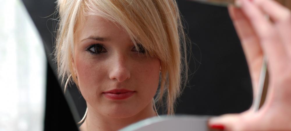 Junge blonde Frau betrachtet sich im Spiegel