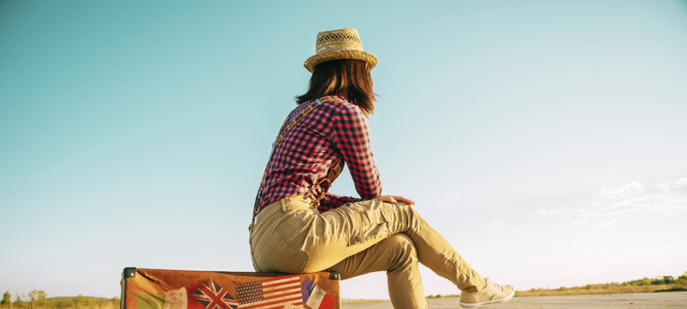 Frau sitzt auf Reisekoffer