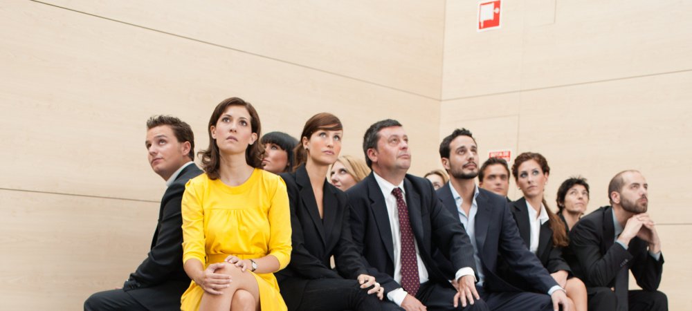 Wartende Business-Menschen unter ihnen eine Frau im knallgelben Kleid