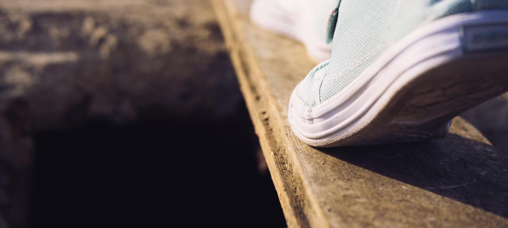 Füße in Turnschuhen balancieren über schmales Brett