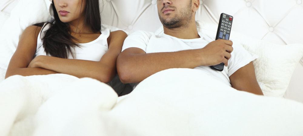 Paar im Bett mit Fernbedienung