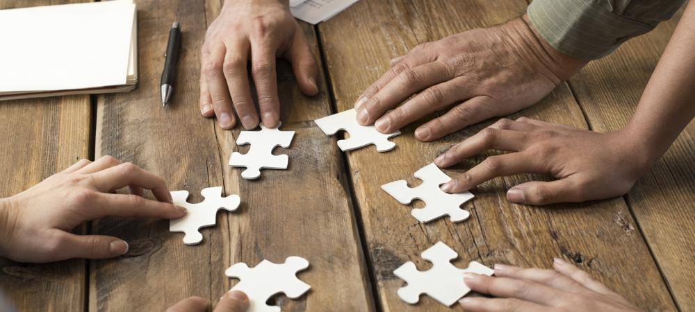 Mehrere Hände mit einzelnen Puzzleteilen, die nicht zusammenpassen