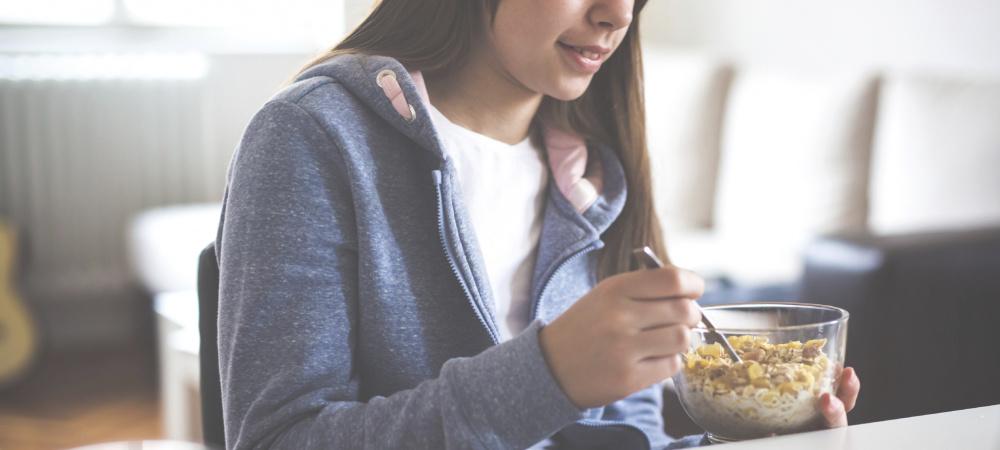 Junges Mädchen isst Müsli am Schreibtisch