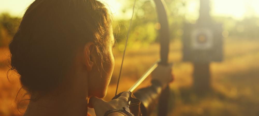Bogenschützin zielt auf Zielscheibe auf dem Feld