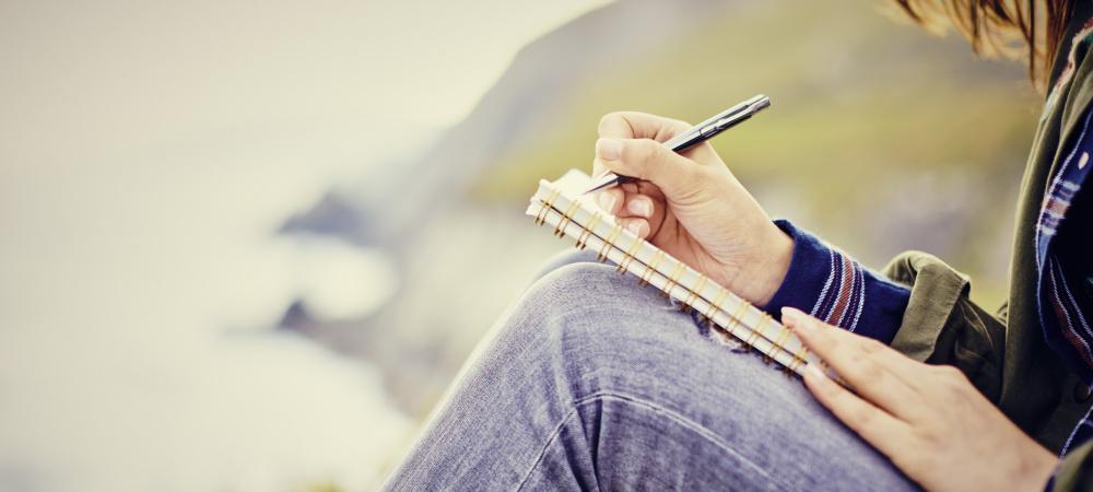 Gute Vorsätze umsetzen: Frau schreibt in Tagebuch