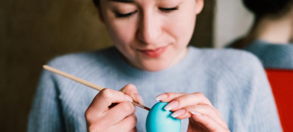 Frau malt Ei blau an
