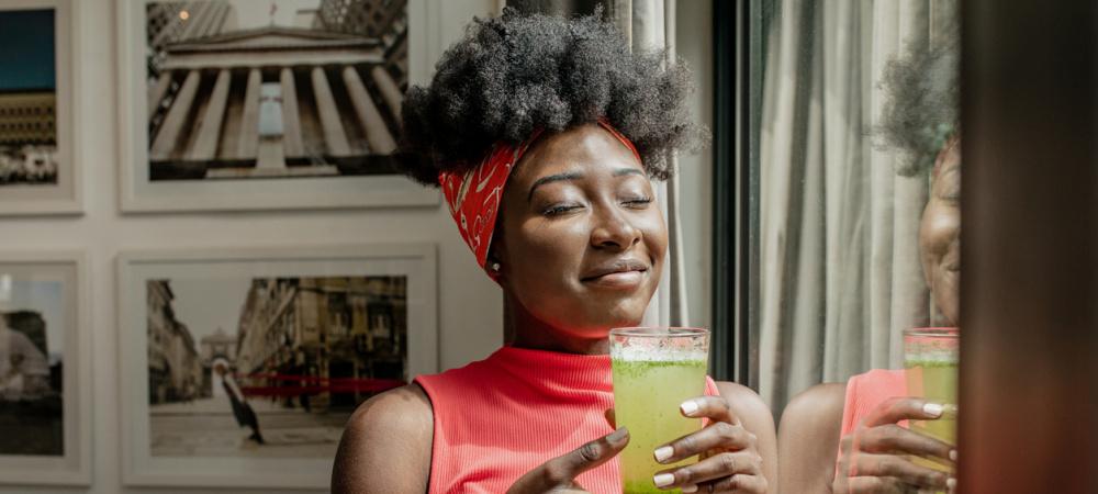 Frau steht am Fenster, Getränk in der Hand