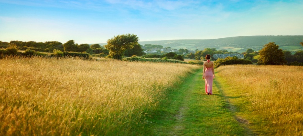 Frau im pinken Kleid auf Feldweg