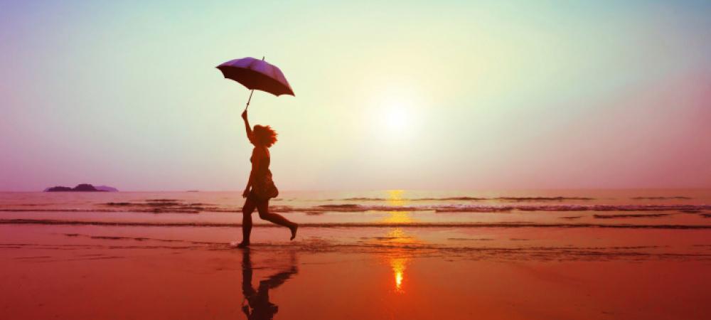 Frau mit Schirm am Strand