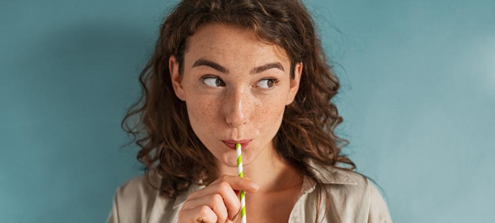 Junge Frau trinkt Smoothie durch einen Strohhalm
