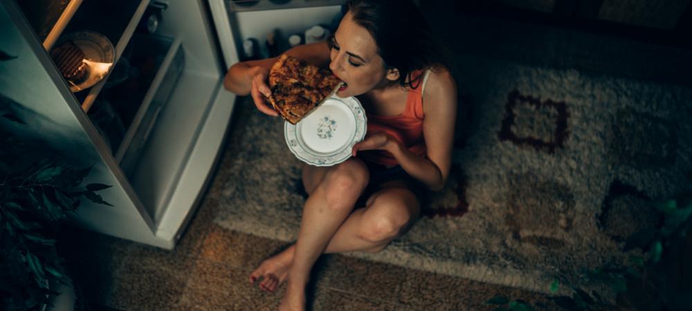 Frau istt Pizza vor geöffnetem Kühlschrank