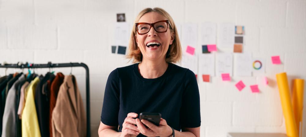 Lachende rau steht mit Handy vor ihrem Schreibtisch