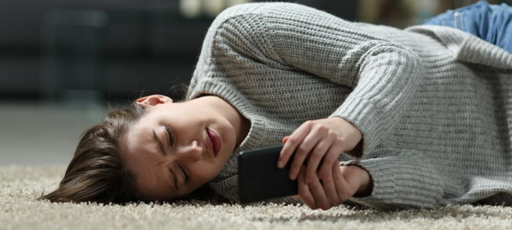 Frau liegt auf dem Boden und schaut traurig aufs Smartphone