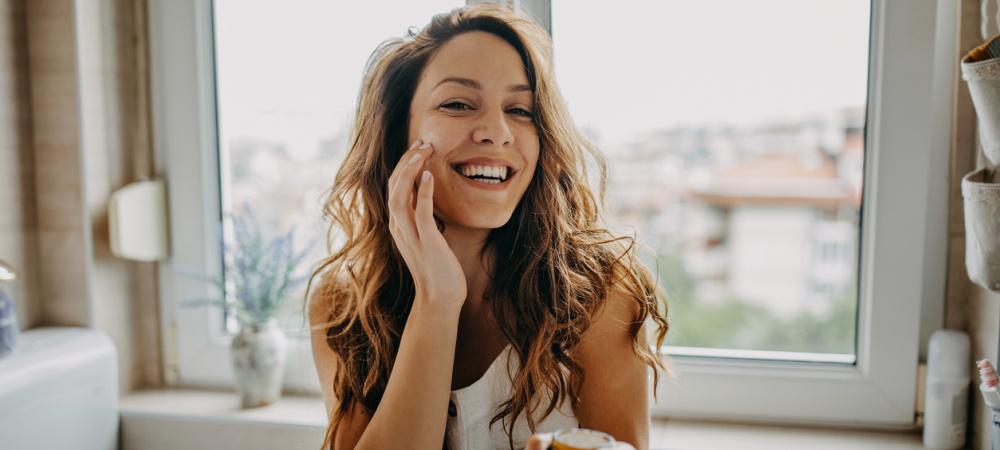 Junge Frau vor dem Spiegel verwendet Gesichtscreme