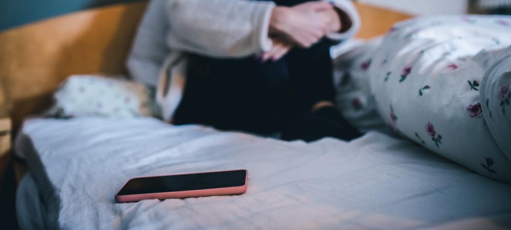 Ein trauriges Mädchen sitzt mit ihrem Handy im Bett.
