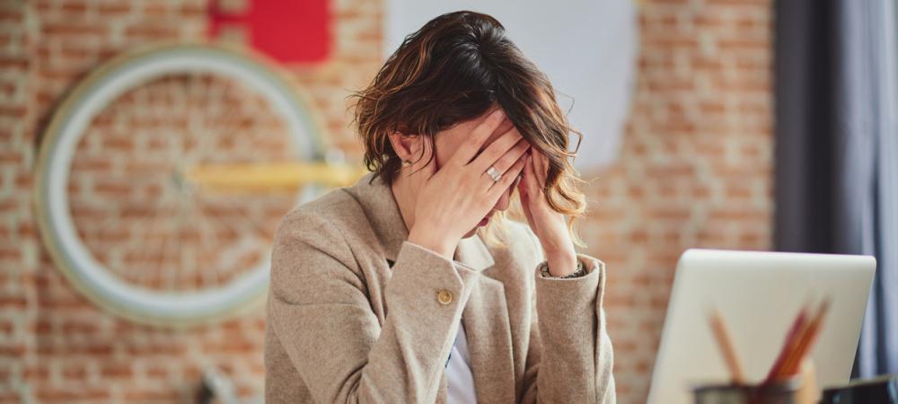 Depressionen im Job: Frau verzweifelt am Schreibtisch
