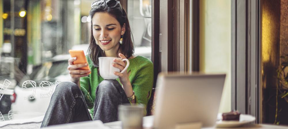 Junge Frau sitzt mit Handy und Laptop im Café.