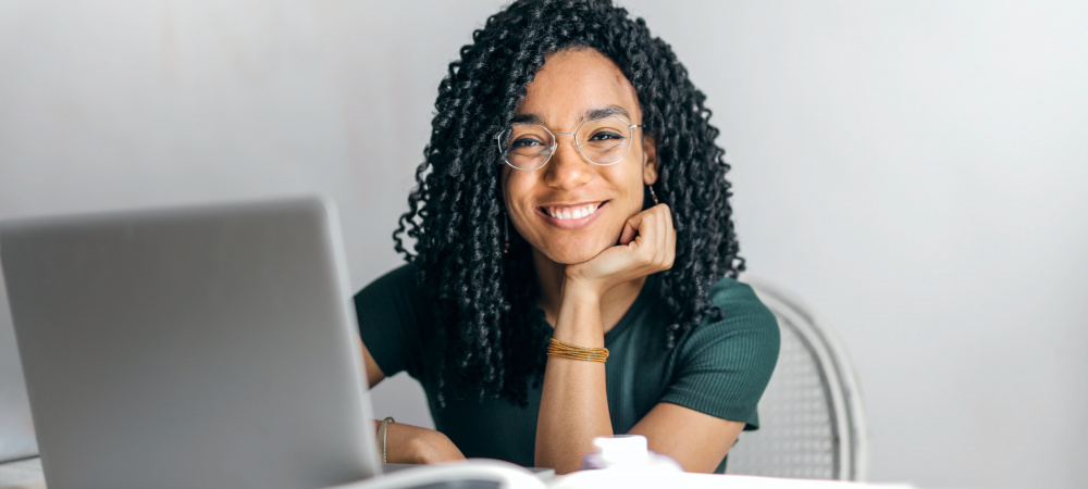 Frau am Laptop lächelt in Kamera