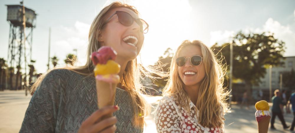 Zwei Freundinnen essen Eis und lachen