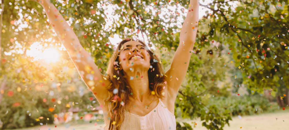 Junge Frau wirft Konfetti im Park