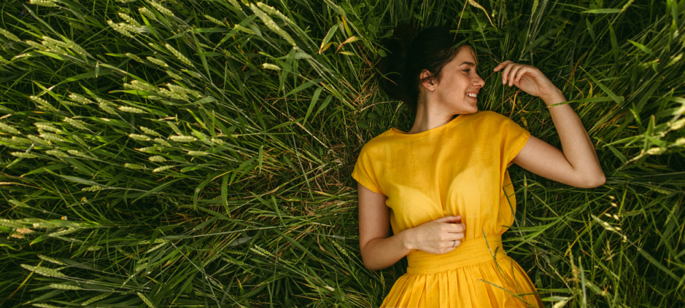Frau mit gelben Kleid im grünen Feld