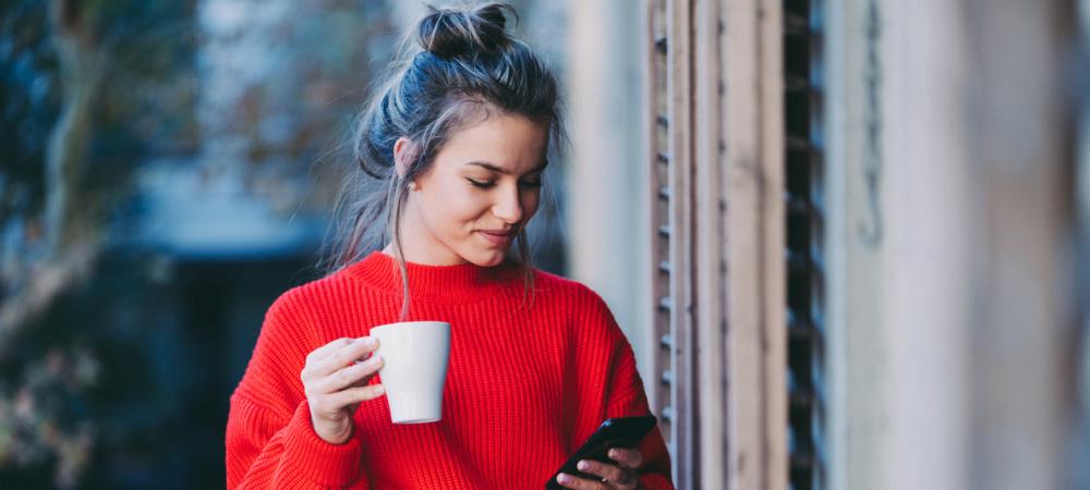 Frau auf Balkon mit kaffee und Handy