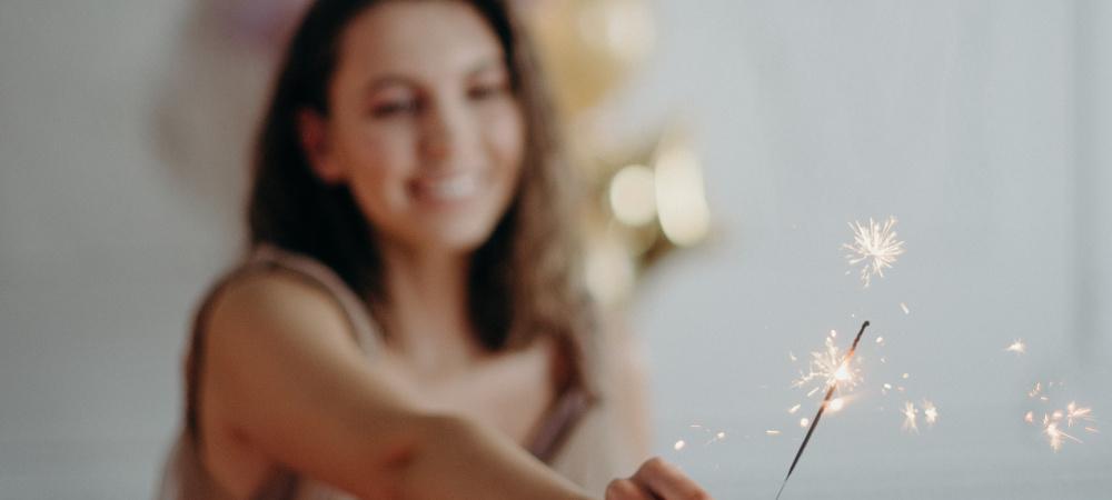 Frau hält Wunderkerze in die Kamera