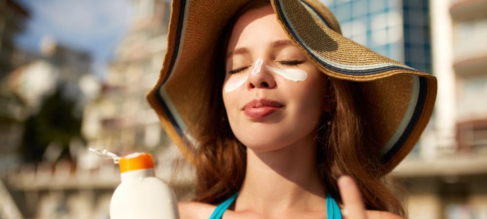 Frau cremt sich mit Sonnencreme ein