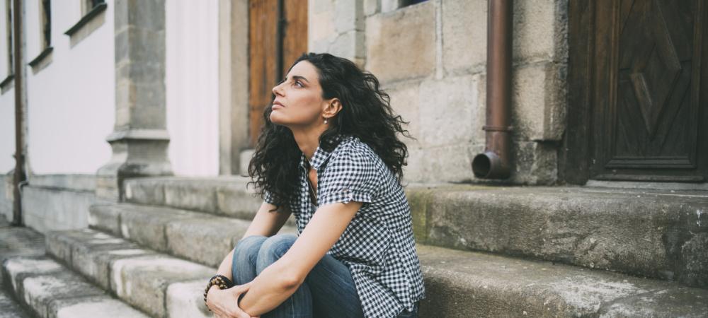 Frau macht sich Sorgen, sitzt auf einer Treppe