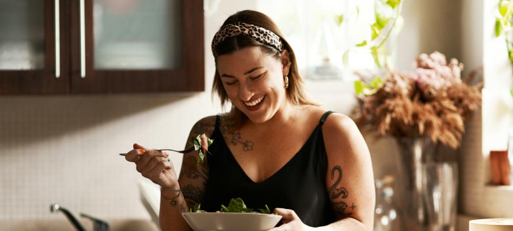 Frau isst Salat in der Küche