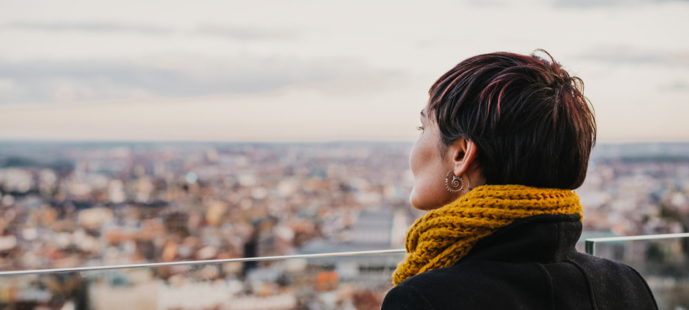 Frau guckt von der Dachterrasse nach unten: Was macht ein gutes Leben aus?