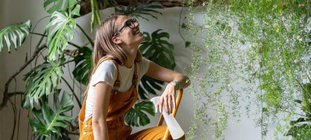 Junge Frau mit Zimmerpflanzen
