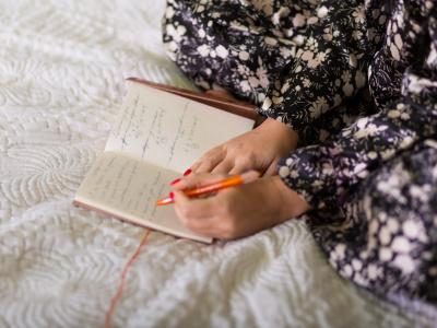 Frau schreibt in Notizbuch