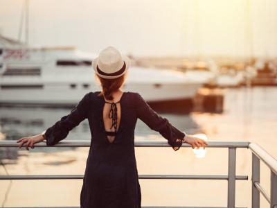 Frau steht am Hafen und guckt auf Yacht