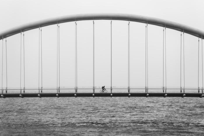 Einsamer Fahrradfahrer auf Brücke