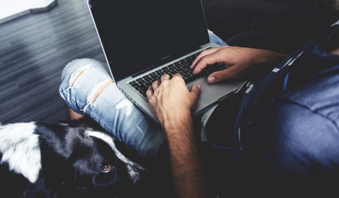 Mann mit Laptop auf den Knien