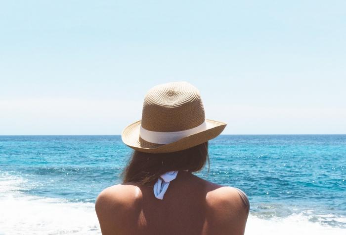Frau mit Hut am Meer