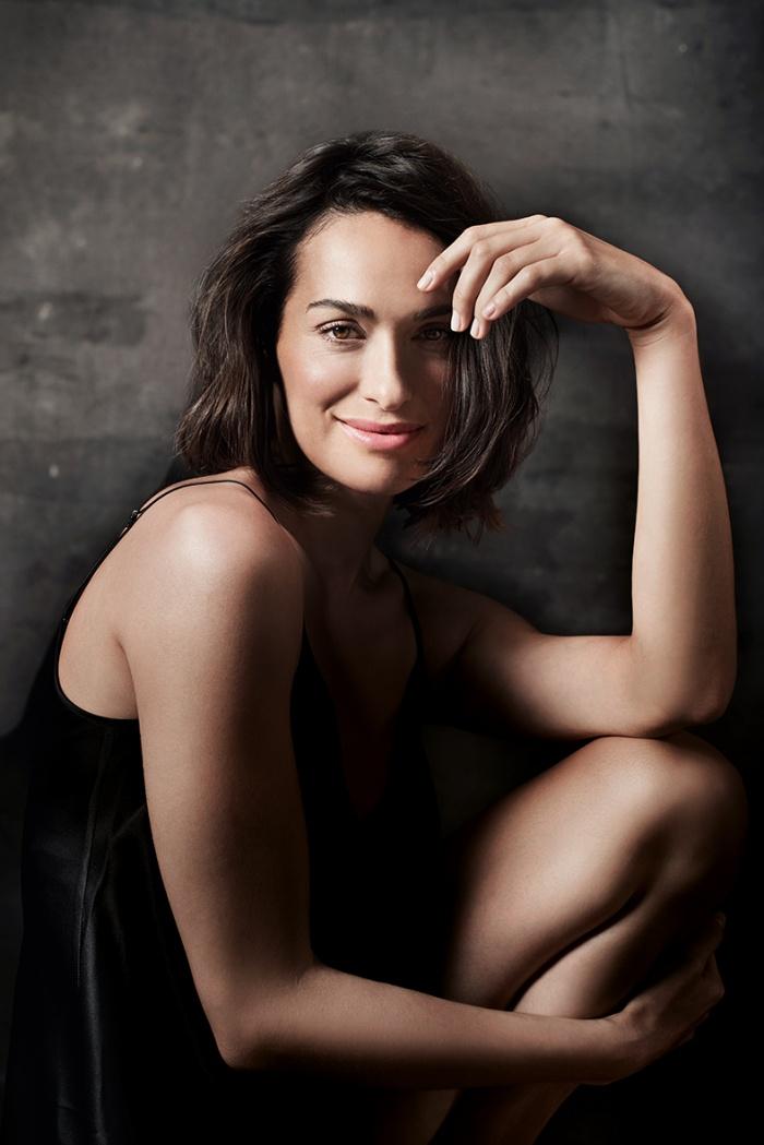 lächelnde Frau in schwarzer Unterwäsche
