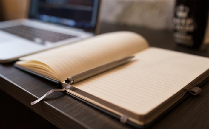 Schreibtisch mit Buch und Stift