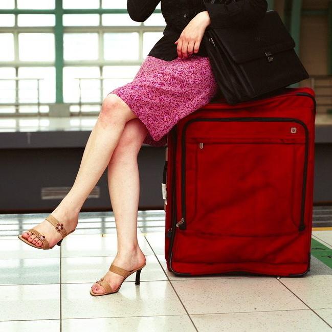 Frau auf Koffer sitzend