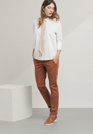 Frau mit rostfarbener Hose
