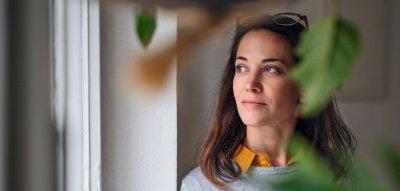 Frau mit Kaffee am Fenster, Grünpflanzen im Vordergrund