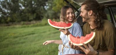 Pärchen sitzt im Auto Kofferraum und isst Wassermelone