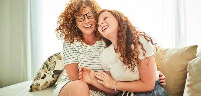 Mutter und Tochter lachen auf dem Sofa