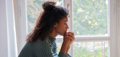 Frau sitzt besorgt am Fenster