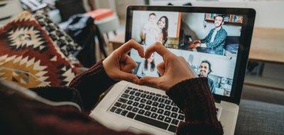 Frau zeigt ein Herz mit ihren Händen vor dem Laptop, Videotelefonat