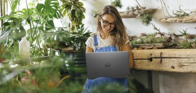 Frau mit Laptop sitzt zwischen Pflanzen und arbeitet