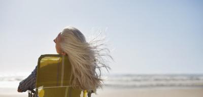 Frau mit grauen langen Haaren sitzt am Meer